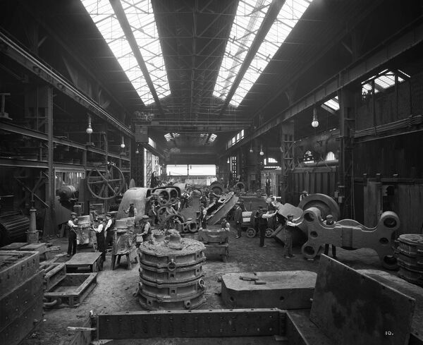 Cammell Laird's Cyclops Ordnance Steel Tyre and Spring Works in Grimesthorpe, Sheffield. Men at work in the fettling shop, with huge components for ships. One of a series of photographs of Cammell Laird works. Bedford Lemere. August 1913