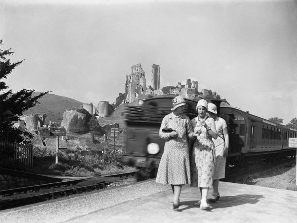Corfe Castle Station, Dorset. Three women on the 'down' platform with Corfe Castle visible in the background and locomotive LSWR Drummond M7, destined for Swanage, pulling away from the platform. Photograph taken between 1925 and 1933