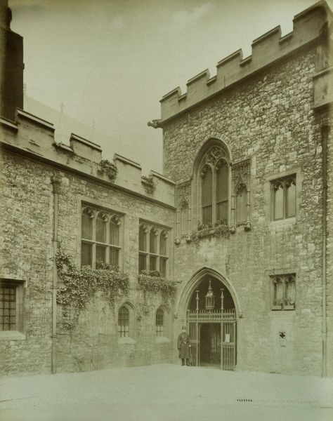 WESTMINSTER ABBEY, London. Entrance to the cloisters from Deans Yard with a policeman standing beside the gate. Photographed in 1886 by Bedford Lemere