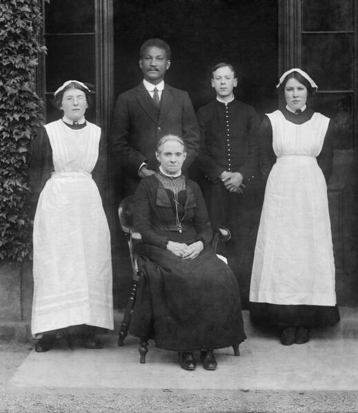 Pembroke College, Oxford. A group of domestic servants posing outside one of the college buildings. A cropped version of image number CC96_00045. Photographed by Henry Taunt