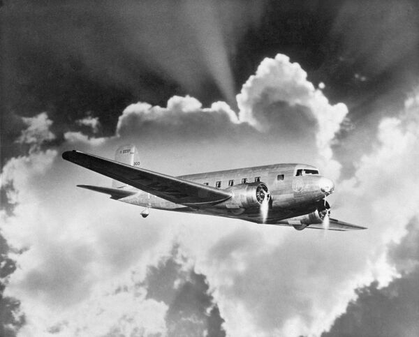 Douglas DC-3 airliner. Advertising image prepared by Aerofilms for a client showing rays of sunshine from behind a cloud.The DC-3 entered civilian service with American Airlines in 1936. Aerofilms Collection (see Links)