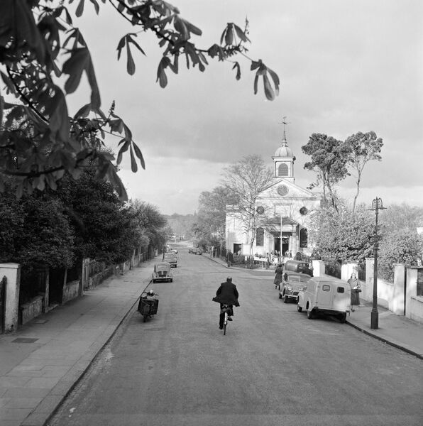 ST JOHNS CHURCH, Downshire Hill, Hampstead, London. A street view looking north east along Downshire Hill towards the entrance front of St John's Church, a cyclist in the middle of the road and cars parked to either side. John Gay. Date range