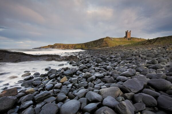 DUNSTANBURGH CASTLE, Northumberland. View of the castle across bouldered beach with overcast sky