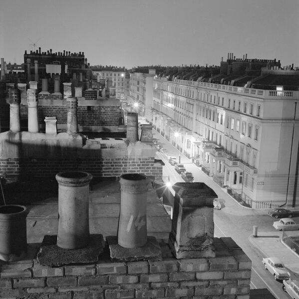 EATON PLACE, Belgravia, Westminster, London. A night time view of the chimney pots to Eaton Place, Belgravia looking over the rooftops and down onto houses on the street below. Photographed by John Gay sometime between January 1962 - May 1964
