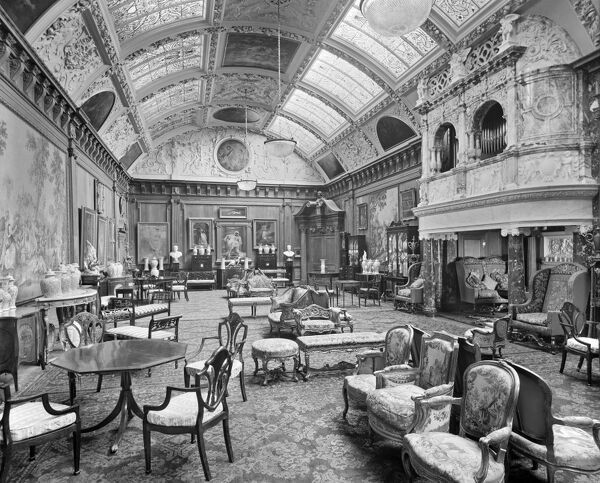 Thornton Manor, near Port Sunlight, Merseyside. Edwardian interior of the music room, which was added in 1902. A large organ is built in over a seating area to the right. Otherwise the room serves as an art gallery, top-lit with windows in the barrel roof