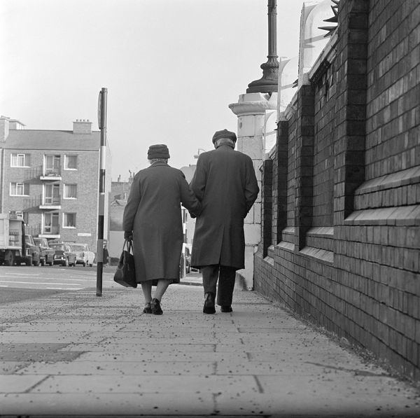 An elderly couple walking away along the pavement next to a high wall in an unidentified road; a modern block of flats in front and parked cars to left, possibly located in Camden, London. A 1960's photograph by John Gay