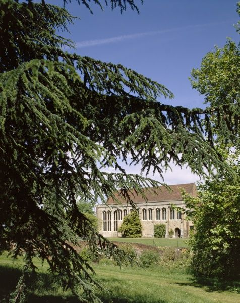 ELTHAM PALACE, Greenwich, London. The gardens in Spring. View of the Great Hall seen through trees