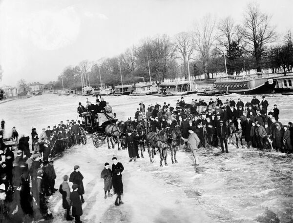 RIVER THAMES near Oxford, Oxfordshire. A crowd of people and horse drawn carriages standing on the frozen River Thames, with barges moored against the bank in the background. Photographed in February 1895 by Henry Taunt