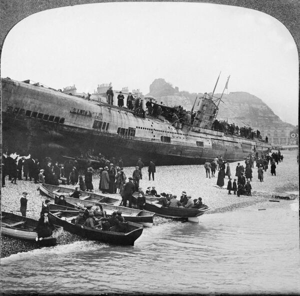 HASTINGS, EAST SUSSEX. People in rowing boats and on the beach, looking up at the German U-boat submarine, U-118, which ran aground on Hastings beach in February 1919