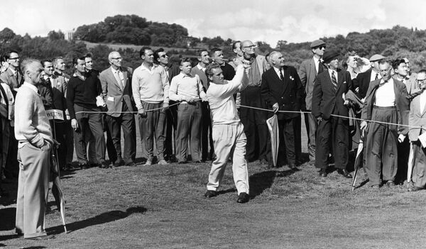 "A professional golfer in full swing during a golf tournament on an unidentified English course. A caddy, to the left, is holding a sign saying ""[S]weetman"". Photographed by Laurence Goldman 1958-61"