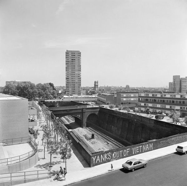 GOSPEL OAK, London. Looking across Southampton Road, showing the railway line passing beneath the road with YANKS OUT OF VIETNAM graffiti on the road bridge and the Ludham and Wendling flats on the Lismore Circus estate visible to either side of the line