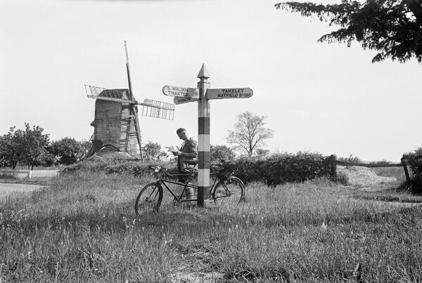 MILL GREEN, Broxted, Essex. A cyclist rests his tandem against the finger post / sign post at Mill Green in Broxted. A windmill stands in the background. Photographed by Herbert Edward Sidney Simmons, 1930's