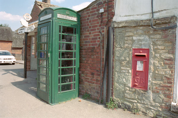 A Dorset street scene of a telephone box, post box and signpost. IoE 403171