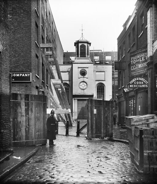 Church Street, Minories, City of London. Timber-frames buttress the wall of a building on Church Street, with a policeman guarding the entrance to the site. You can also see the west front of Holy Trinity Minories beyond, which was closed as a church in 1899