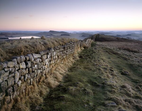 HADRIAN'S WALL, Northumberland. The path along Hotbank Crags at dawn, with Greenlee Lough in the distance. hadrian