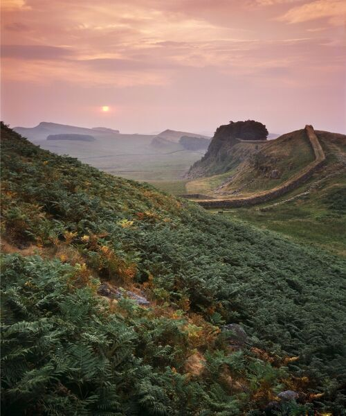 HADRIAN'S WALL, Northumberland. The sun sets in the sky showing the wall stretching off into the distance. hadrian