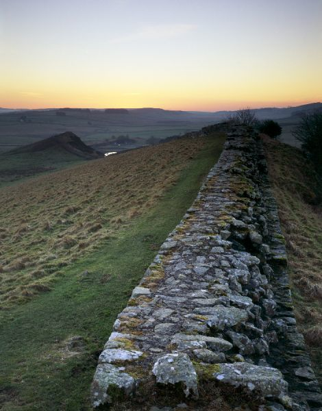 HADRIAN'S WALL, Northumberland. Cawfield Crags, west of turret 41B. View of the wall stretching towards Whin Sill and Cawfields Quarry as the sunsets, illuminating the sky. hadrian