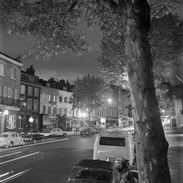 HIGH STREET, Hampstead, London. Parked cars and traffic in Hampstead High Street at night. Photographed by John Gay. Date range: 1960 - 1965