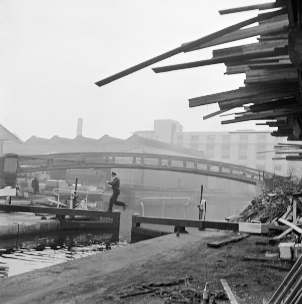 HAMPSTEAD ROAD CANAL LOCK, Regents Canal, Camden Town, Greater London. A view of Hampstead Road Lock, showing in the foreground a uniformed man jumping from one opening lock gate to the other, a roving bridge in the midground and canal warehouses beyond