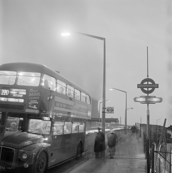HARLESDEN, Greater London. A street scene with a No. 220 bus at a bus stop by a London Underground station sign in Harlesden at night, people waiting and cars passing, with the North Acton power station to the south of Harlesden Station in the background