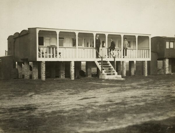 Converted railway carriage holiday home, possibly at Shoreham-by-Sea, West Sussex. Silver gelatin DOP (developing out paper) print by an unknown photographer, 1920s. Holidaymakers pose on the verandah of their converted railway carriage holiday home