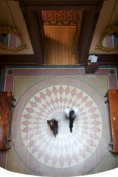 KENWOOD HOUSE, London. Interior view. Two visitors walking across the Lobby viewed from above showing the floor covering, 2006