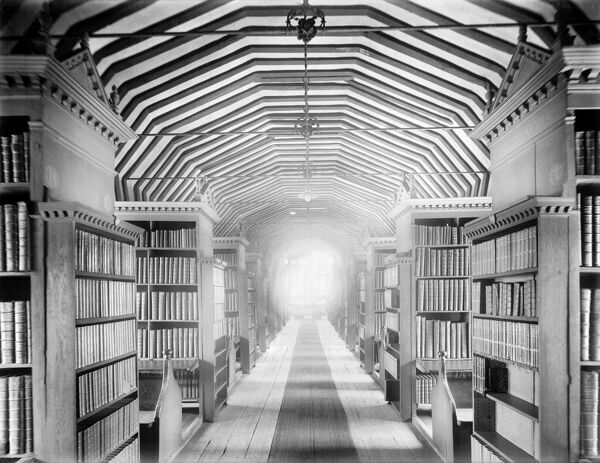 LIBRARY, ST JOHN'S COLLEGE, Oxford, Oxfordshire. The interior of the old library in Canterbury Quad, built in 1596-1601, showing rows of bookcases leading up to the large window at the east end. Photographed by Henry Taunt in 1916