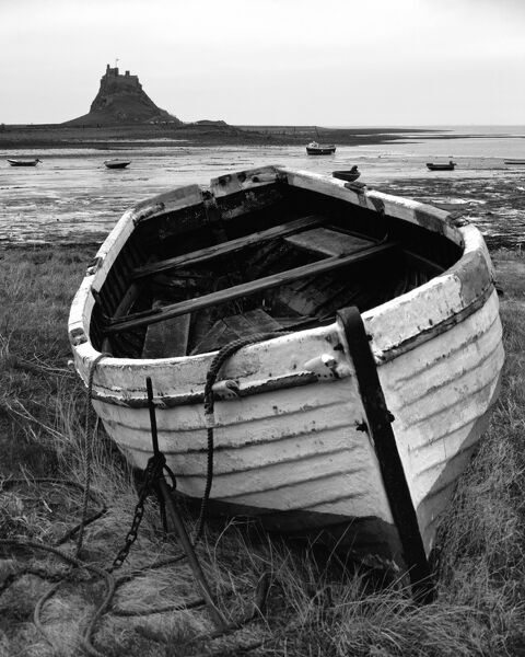 LINDISFARNE CASTLE, Holy Island, Northumberland. Decaying fishing boat with the castle in the background - monochrome