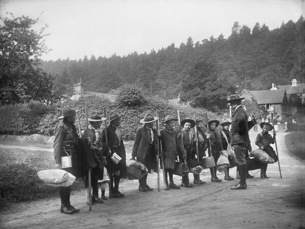 A line of boy scouts and their scout master standing on a road in Holmbury St Mary, Surrey. The scouts are carrying scout staffs and bedrolls for a camping or pioneering trip. Photographed by Katherine J. Macfee, 23rd May 1912