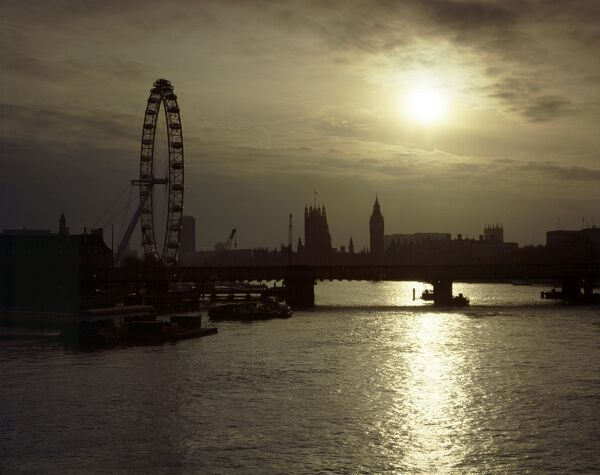 THE LONDON EYE, London. View looking towards the London Eye and the Houses of Parliament from Waterloo Bridge