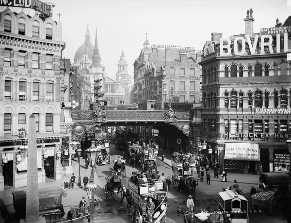 LUDGATE CIRCUS, City of London. A busy street view of Ludgate Circus looking towards St Paul's Cathedral with horse-drawn buses in the foreground and a steam train on the bridge. The Circus was constructed at the junction of Ludgate Hill