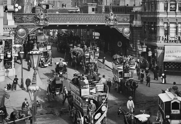 LUDGATE CIRCUS, City of London. A busy street view of Ludgate Circus with horse-drawn buses in the foreground and a steam train on the bridge. The Circus was constructed at the junction of Ludgate Hill and Fleet Street between 1864 and 1875