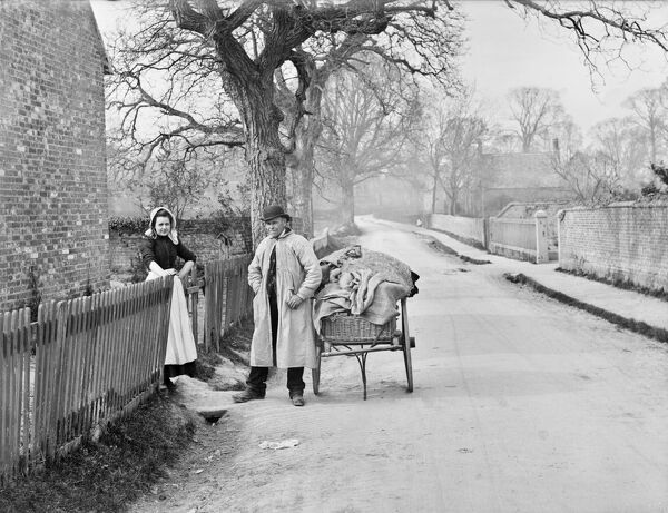 MOULSFORD, Oxfordshire. A man in a smock with a hand-drawn cart piled with cloth meeting a young woman at the gate to a house, called by Taunt 'smockfrock and skirtie'. Photographed by Henry Taunt in 1895