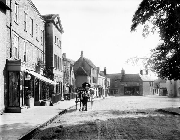 MARKET PLACE, Fairford, Gloucestershire. A woman in a horse and trap outside a clothier's shop in the picturesque cotswold town. Photographed in 1890 by Henry Taunt