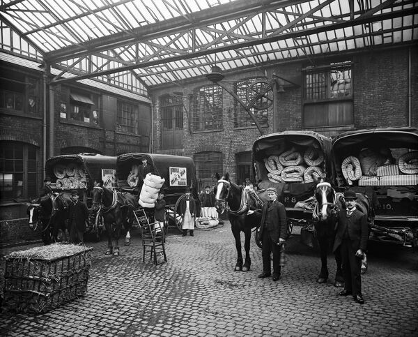 HEAL AND SON LIMITED, 195-199 Tottenham Court Road, London. Staff and horse-drawn wagons loaded with mattresses and bedding made at the site, posing in the courtyard. Commissioned by Heal and Son Ltd, this photograph was taken by Bedford Lemere and Co