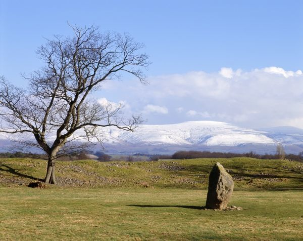 MAYBURGH HENGE, Cumbria. View towards the standing stone located in the middle of the henge showing snow fall on the fells behind