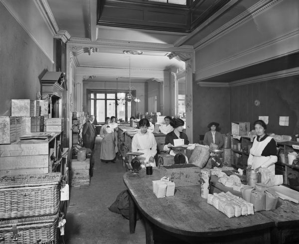 National Food Fund building on Dover Street, Westminster. The National Food Fund processed donated food to feed thousands of Belgian war refugees. Women packing groceries. Bedford Lemere, 1915