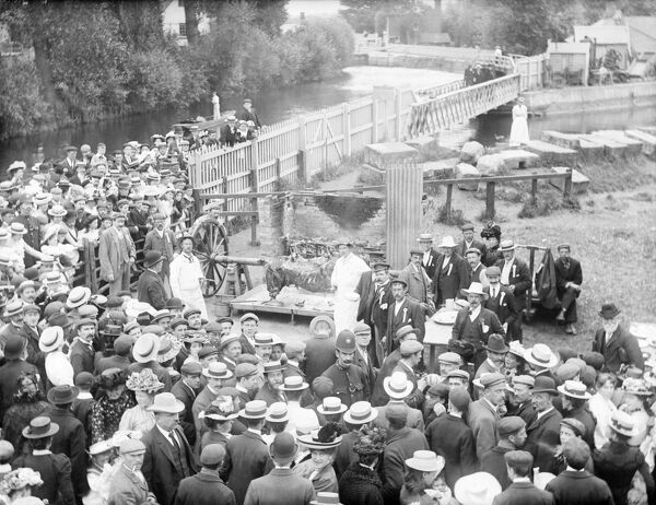 OSNEY BRIDGE, Oxford. A large crowd of people gathered for an ox-roast to celebrate the coronation of Edward VII, with the river Thames in the background. Photographed by Henry W Taunt in 1902