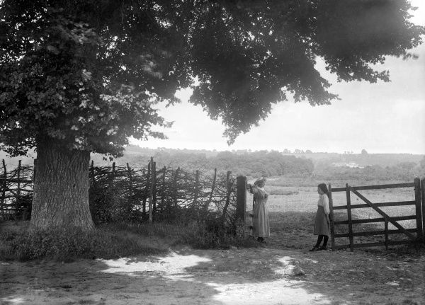 OPEN BRASENOSE, Horspath, South Oxfordshire. A picturesque view of the Oxfordshire countryside, showing two women standing by a gate. Photographed by Henry Taunt in July 1916