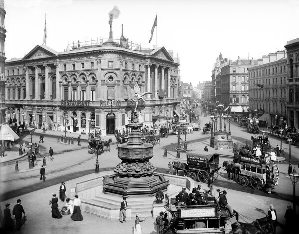 PICCADILLY CIRCUS, Westminster, London. A view of Piccadilly from the west looking towards Coventry Street and showing the London Pavilion. The statue of Eros stands in the middle of a busy Piccadilly Circus with horse-drawn vehicles in the foreground