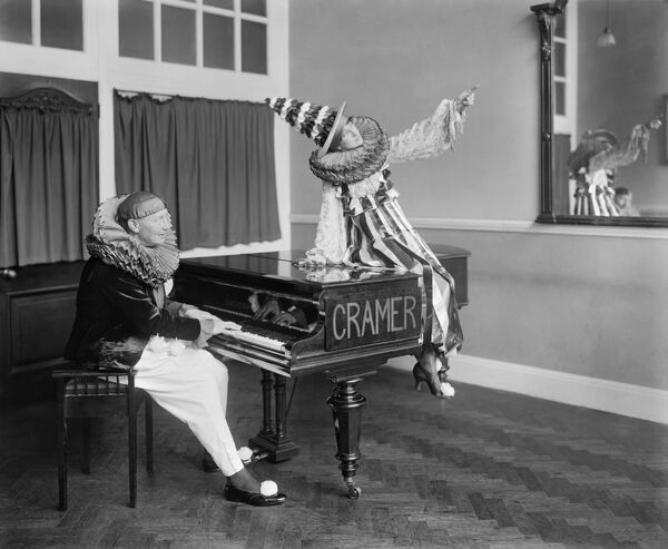 Two Pierrot clowns performing a routine with a piano