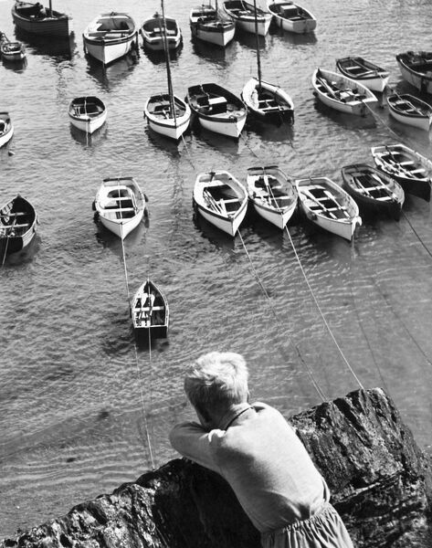 PORTSCATHO HARBOUR, Gerrans, Cornwall. A young boy looking down towards tethered boats in the harbour at Portscatho. Photographed by John Gay during 1950s-1960s
