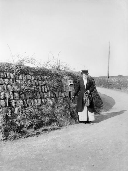 This woman, working as a post lady, is emptying a post box at an unidentified location in Kerrier, Cornwall