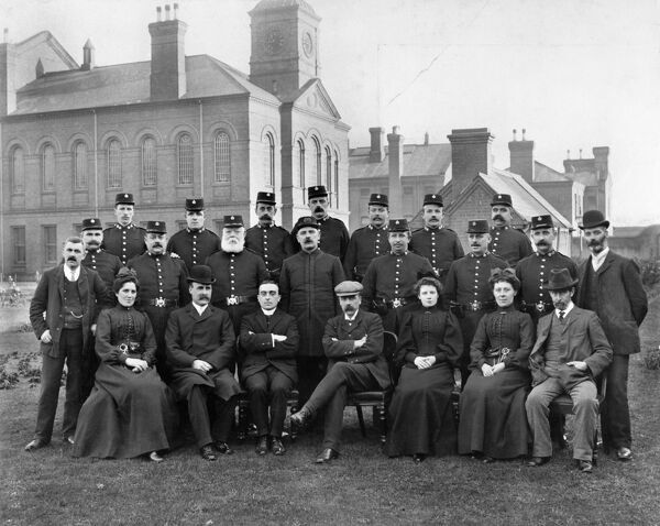 A group portrait of staff and warders at Nottingham Prison. The prison was built in 1889-91 for both male and female prisoners, hence the female warders in this photograph which was probably taken soon after it opened. The administration block and chapel