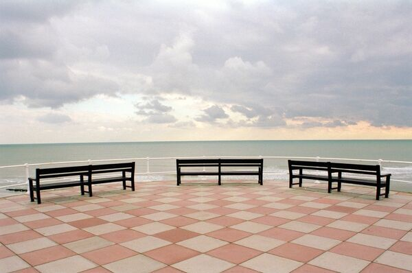 THE PROMENADE, Hastings, East Sussex. A view looking across three benches on the promenade and out to sea. The promenade stretches along three miles of the shore. It was rebuilt in the 1920s and 1930s