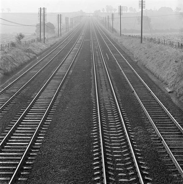 Railway track, Hertfordshire. An elevated view of four parallel railway tracks running into the distance, with electricity or telephone pylons running at each side beside farmed fields. Photographed by John Gay. Date range: 1955-1965