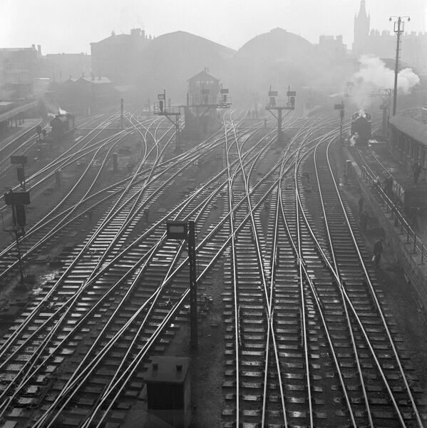 KINGS CROSS, London. An elevated viewpoint of the railway track to the north of Kings Cross Station, a steam engine on the tracks to either side and St Pancras Station in the far distance. John Gay. Date range: 1946-1969