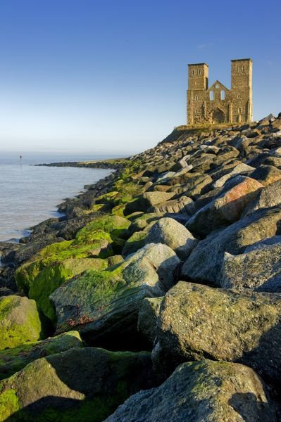 RECULVER TOWERS AND ROMAN FORT, Kent. View of the twin towers with rocks of hard coastal defences in the foreground
