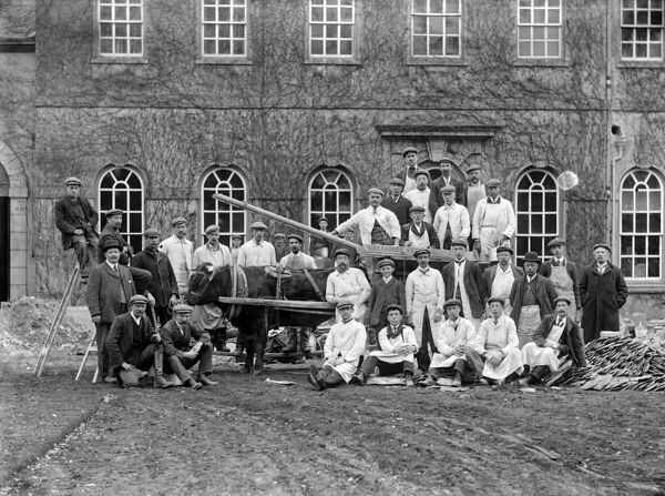 Kingston Lisle House, Kingston Lisle, Oxfordshire. A large group of workmen posing outside a house with a bullock cart, during renovation work. A pile of roof tiles can be seen on the right of the picture. Photographed by Henry Taunt c.1900