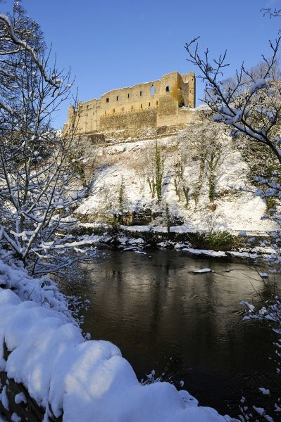 RICHMOND CASTLE, North Yorkshire. View across the River Swale showing Scolland's Hall perched above the river. Snow covered landscape